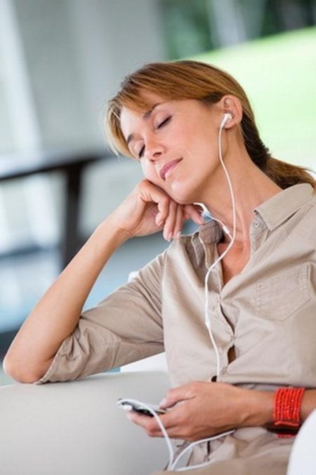 portrait de femme qui coute de la musique avec des oreillettes